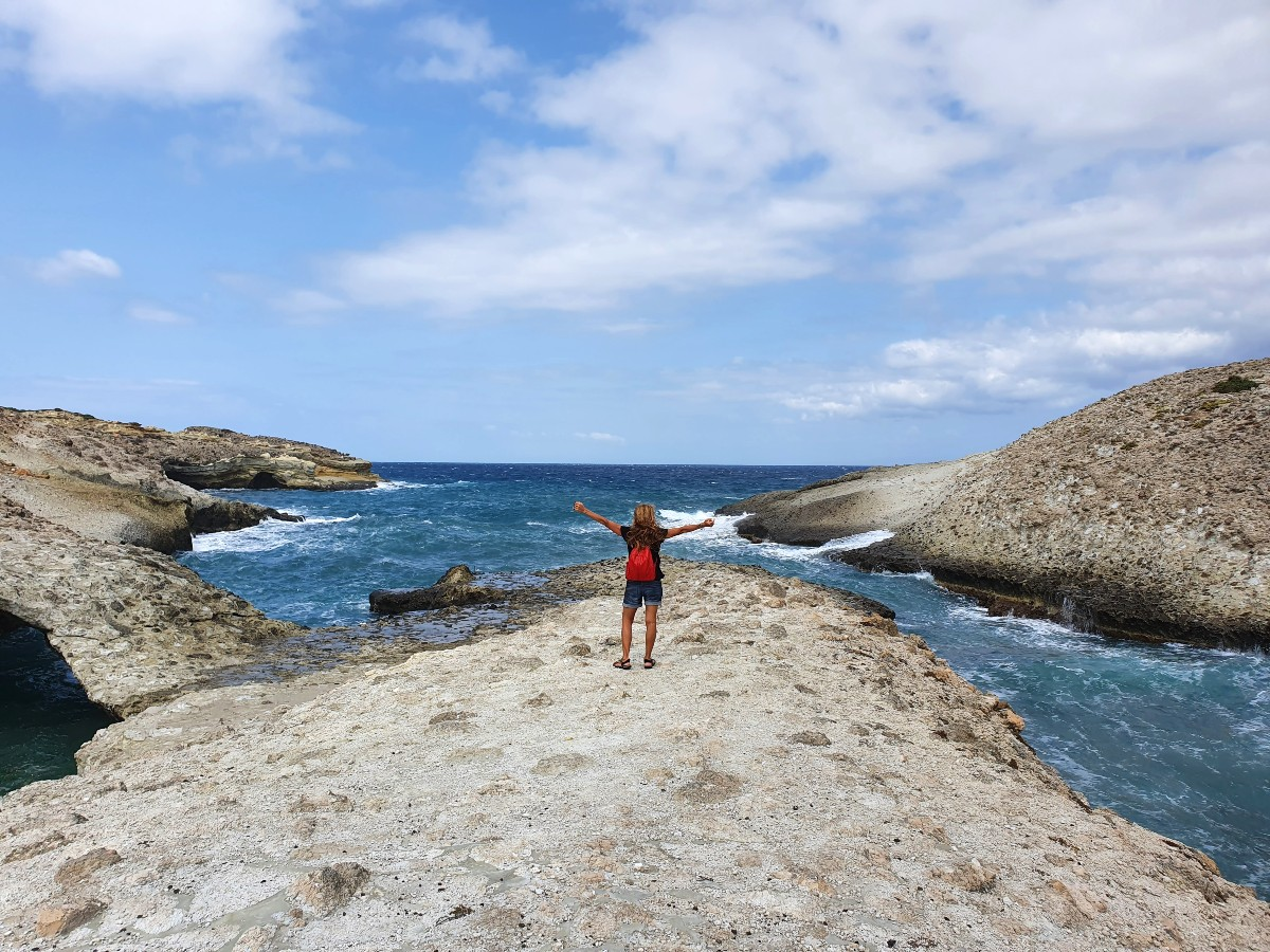 Vanessa from Real Greek Experiences standing on a wild beach in Kimolos Greece